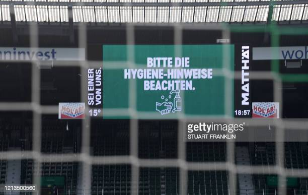 "Screen displays the words ""Follow the hand hygiene"" above the empty stands prior the German first division Bundesliga football match Werder Bremen v..."