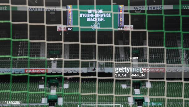 """Screen displays the words """"Follow the hand hygiene"""" above the empty stands prior the German first division Bundesliga football match Werder Bremen v..."""
