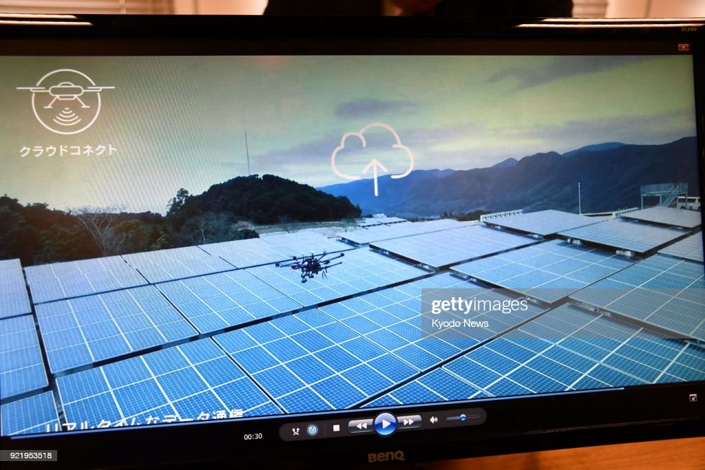 A screen in Tokyo on Feb. 21, 2018, shows a remote-controlled drone of Japanese mobile phone operator NTT Docomo Inc. flying over solar panels. The company said the same day it will launch a business related to its drone operating system dubbed 'docomo sky.' ==Kyodo