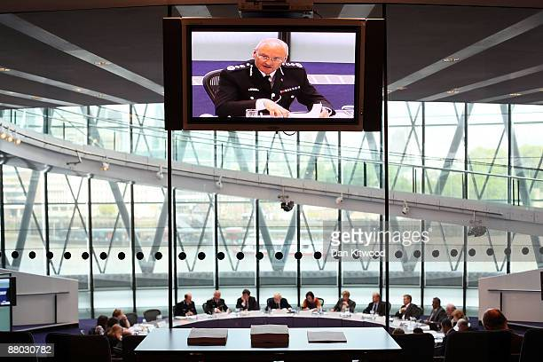 Screen projects a picture of Commisioner Sir Paul Stephenson as he meets with Mayor Boris Johnson and members of the Metropolitan Police Authority at...
