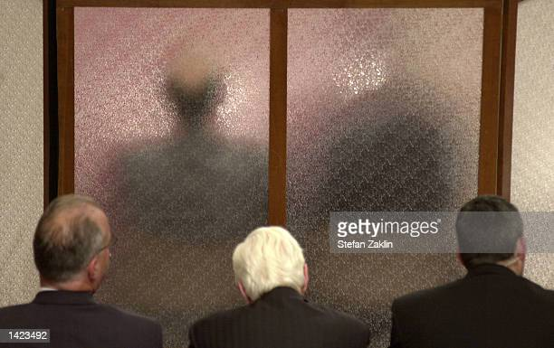 A screen separates and protects two counter intelligence agents from observers and the media during a Senate and House Select Committee on...