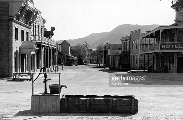 A screen set with a town water pump and horse watering trough built for a western film at Hollywood Los Angeles California Original Publication...