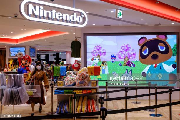 Screen showing the characters from the Animal Crossing series video game is seen at a Nintendo store in Tokyo on June 10, 2020.