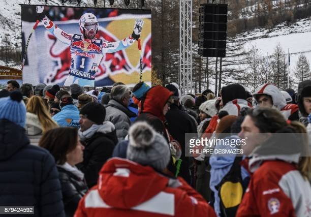 A screen shows a photo of late French skier David Poisson as people attend a ceremony in his memory in PeiseyNancroix in the French Alps on November...