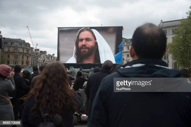 A screen shows actor James BurkeDunsmore playing the role of Jesus Christ being 'crucified' on the cross during a performance of Wintershall's 'The...