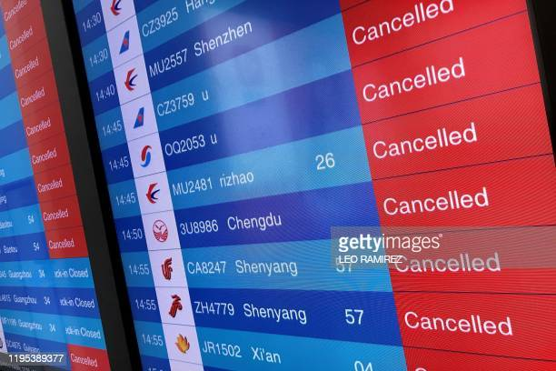 A screen shows cancelled flights is pictured at Tianhe airport in Wuhan in China's central Hubei province on January 23 2020 China banned trains and...