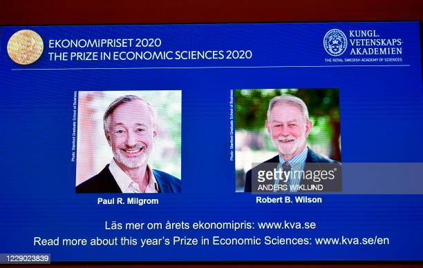 """Screen shows pictures of US economists Paul Milgrom and Robert Wilson during the announcement of the winners of the """"2020 Nobel Prize Sveriges..."""