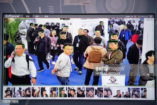 A screen shows visitors being filmed by AI security cameras with facial recognition technology at the 14th China International Exhibition on Public...