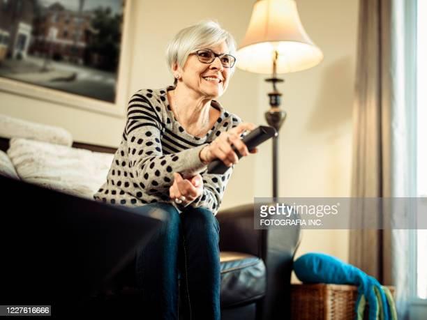 bildschirmzeit, großmutter mit fernbedienung - insight tv stock-fotos und bilder