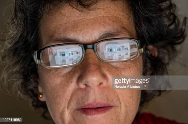 Screen with students' work is reflected in the eyeglasses of professor Luisa Ferreira as she gives a virtual photojournalism class via Zoom from her...