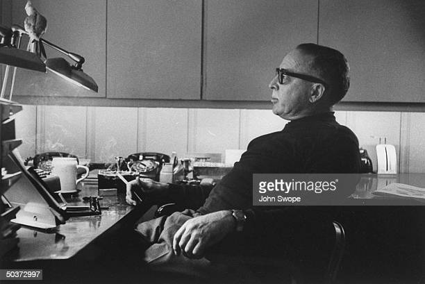 Screen writer and director Dalton Trumbo sitting at his desk holding a cigarette and gazing thoughtfully at his pet bird perched on a lamp