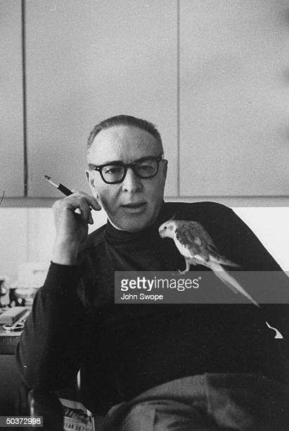 Screen writer and director Dalton Trumbo sitting at his desk holding a cigarette with his pet bird perched on his chest