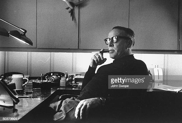Screen writer and director Dalton Trumbo smoking cigarette in holding sitting thoughtfully at his desk