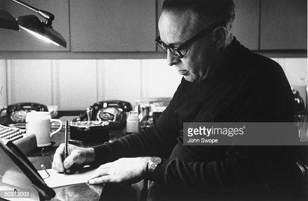 Screen writer and director Dalton Trumbo writing in longhand at his desk