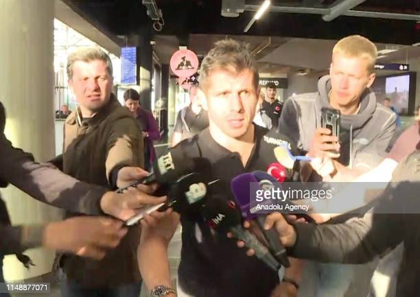 A screengrab captured from a video shows a man holding a toilet brush to Emre Belozoglu of Turkish National Football Team as he speaks to media upon...