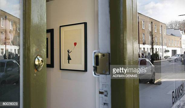 A screenprint entitled 'Girl with Balloon' by the artist 'Banksy' is pictured through an open door during a gallery photocall at the Andipa Gallery...
