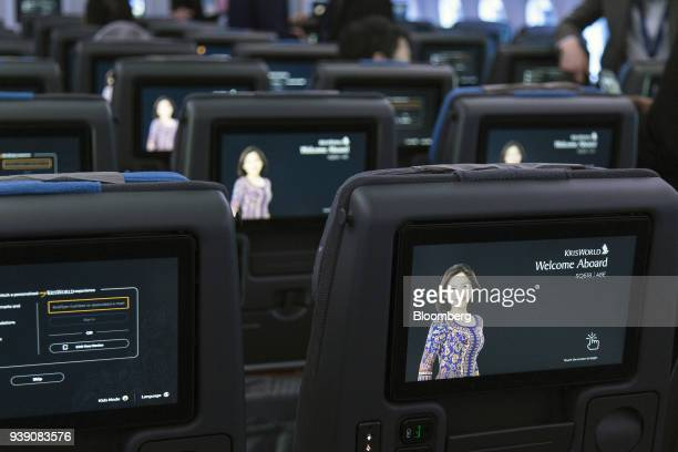 Screens are seen on the back of economy class seats onboard a Boeing 78710 Dreamliner aircraft operated by Singapore Airlines Ltd at Changi Airport...
