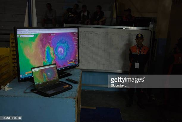Screens display meteorological forecasts as an official stands by in a gym ahead of Typhoon Mangkhut's arrival in Tuguegarao Cagayan province the...