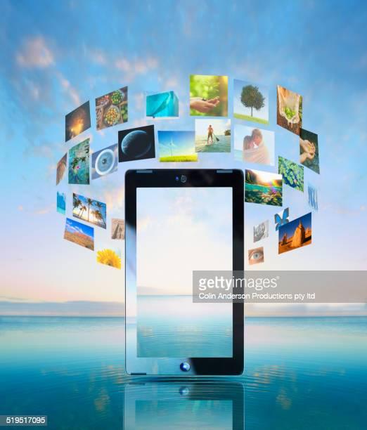 Screens floating around digital tablet over water
