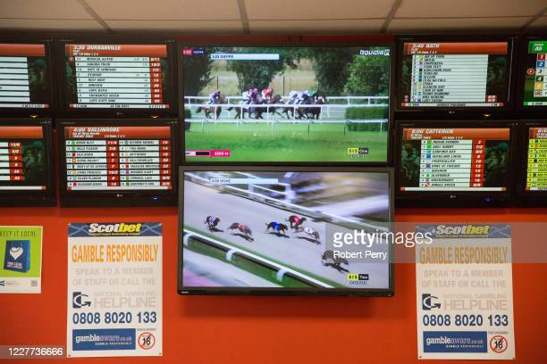 Screens show horse and dog racing at the Scotbet Independent bookmakers shop, as coronavirus measures are relaxed to allow televisions and seating...