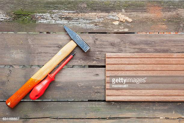screw driver and hammer lying on rotten balcony floarboards - floorboard stock photos and pictures