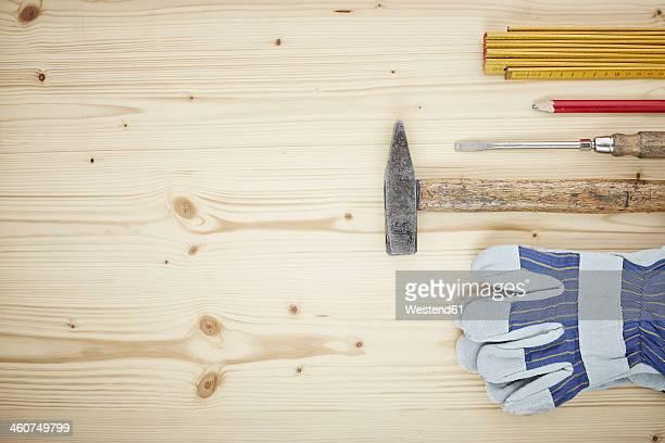 Screwdriver, work glove, pencil, folding ruler, hammer on wood, close up