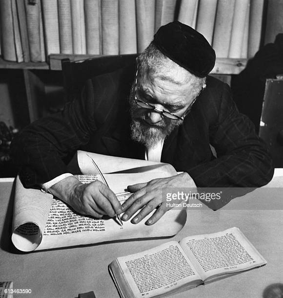 A scribe copies the calligraphy of the Torah from a book onto the scroll