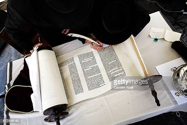 A scribe pens the final letters on a newly dedicated Torah scroll in the Chabad Synagogue on May 7 2015 in Berlin Germany The ceremony will take...