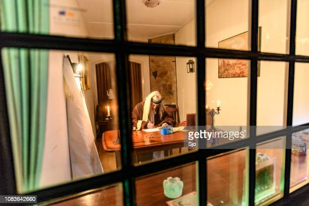 scrooge from dickens a christmas carol counting his money behind his desk - ebenezer scrooge stock photos and pictures