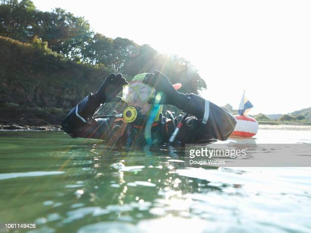 scuba diver adjusting mask before diving. - dougal waters stock pictures, royalty-free photos & images