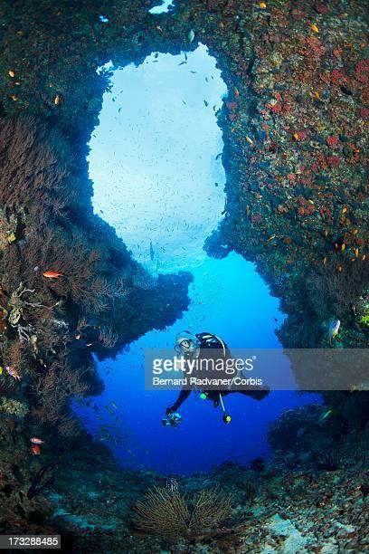 scuba diver at a cave entrance