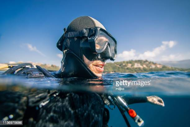 scuba diver at sea surface - aqualung diving equipment stock pictures, royalty-free photos & images