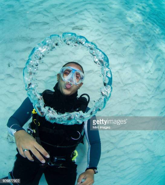 scuba diver blowing bubble rings. as the escaping air rises to surface, the decrease in pressure causes the rings of air to expand. - kreis stock-fotos und bilder
