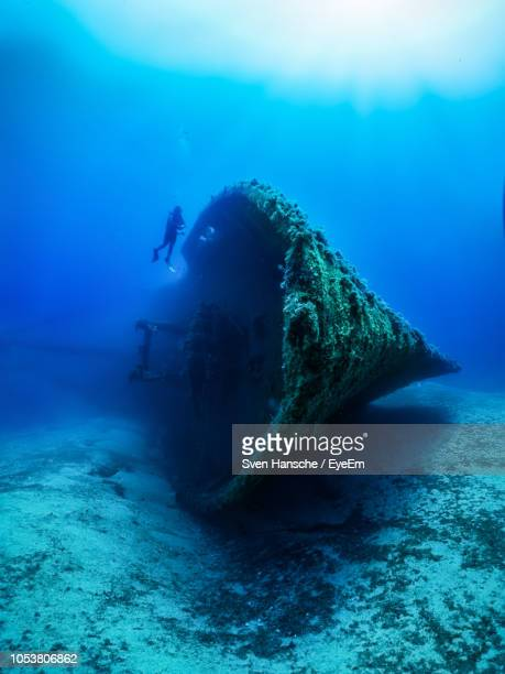 scuba diver by shipwreck in sea - shipwreck stock pictures, royalty-free photos & images