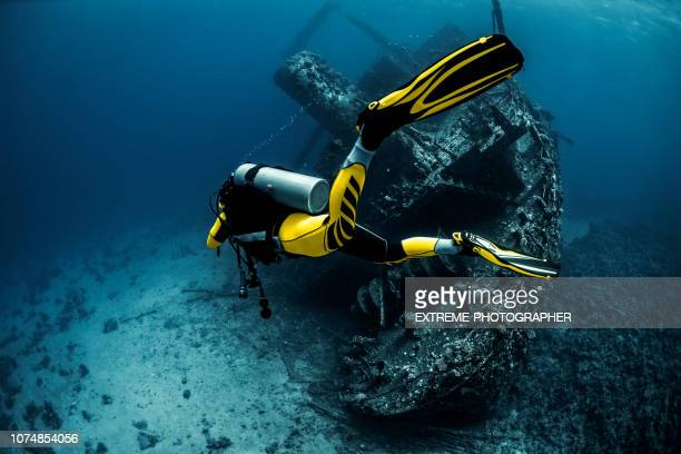 scuba diver circling a rusty old underwater shipwreck in the red sea - sunken stock pictures, royalty-free photos & images
