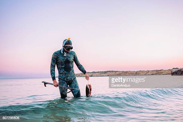scuba diver coming back from spear fishing