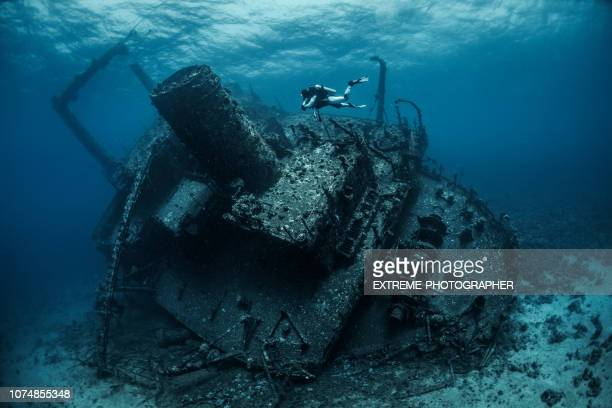scuba diver diving above an underwater overgrown shipwreck in the red sea - sunken stock pictures, royalty-free photos & images