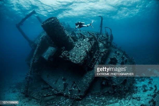 scuba diver diving next to a large shipwreck under the red sea - shipwreck stock pictures, royalty-free photos & images
