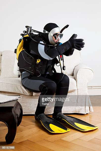 A scuba diver diving off a couch in a living room