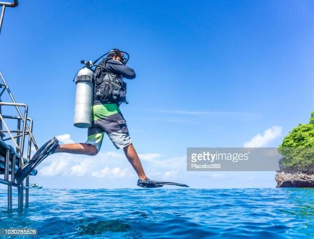 scuba diver doing giant stride entry into sea - water sport stock photos and pictures