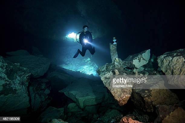 scuba diver enters ben's cave. - lucayan national park stock photos and pictures