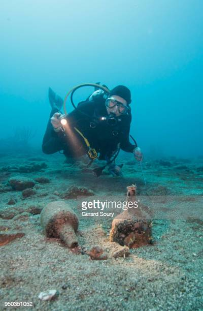 scuba diver examining old bottles from a sailboat shipwreck - 古代の遺物 ストックフォトと画像