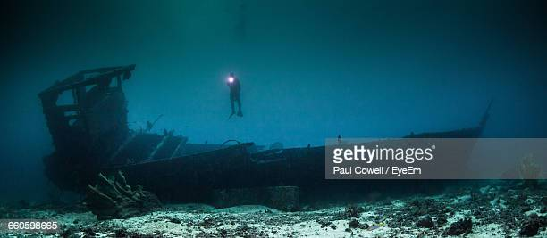 scuba diver explores wreck in undersea - sunken stock pictures, royalty-free photos & images