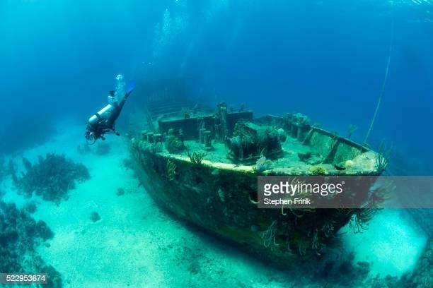 scuba diver exploring a large shipwreck - restos de un accidente fotografías e imágenes de stock