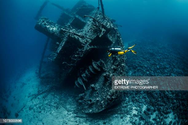 scuba diver exploring a shipwreck under the red sea - aqualung diving equipment stock pictures, royalty-free photos & images