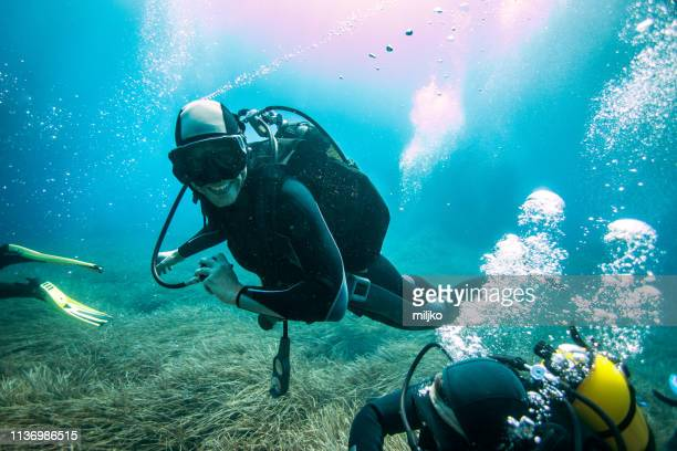 scuba diver exploring sea bottom - aqualung diving equipment stock pictures, royalty-free photos & images