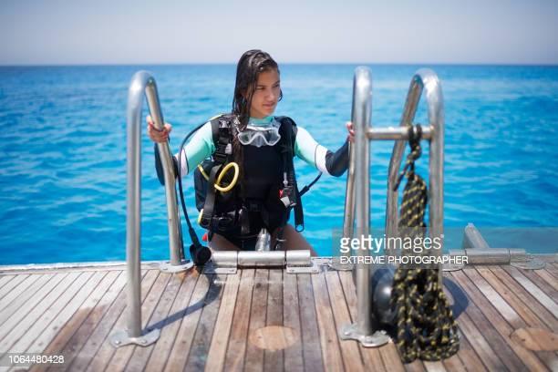 Scuba diver girl climbing