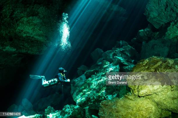 scuba diver in cenote light rays - spelunking stock pictures, royalty-free photos & images