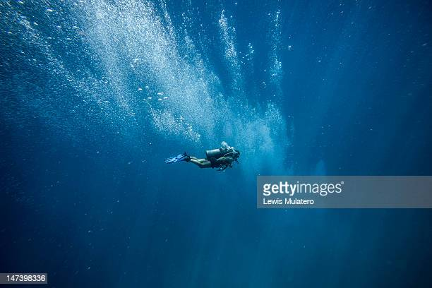 Scuba diver in deep open ocean with oxygen bubbles