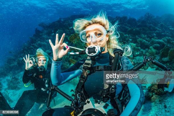 スキューバ ダイビングを探索し、珊瑚礁の海生活スポーツ女性水中写真家カップル 2 つを楽しんで - スクーバダイビングの視点 ストックフォトと画像